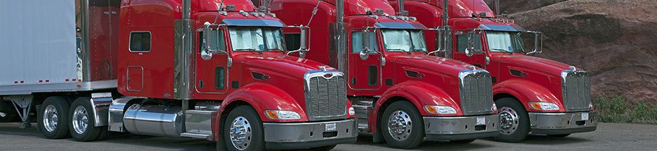 Three red semi trucks parked next to each other | improve CSA scores