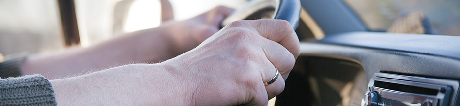 A close-up of a driver holding a steering wheel | manage accident risk