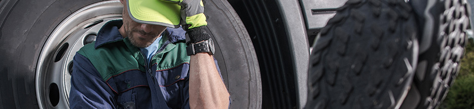 A driver leans against his truck tire as he takes a break | Rising Insurance Premiums for Transportation Firms